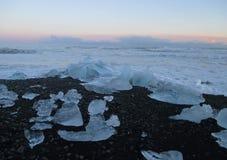 Roztapiające góry lodowa na czarnym piasku wyrzucać na brzeg pod pięknym zmierzchu niebem Obrazy Stock