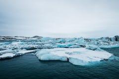Roztapiający lód na wodzie w Jokulsarlon jeziorze w południowym Iceland w chmurnym dniu globalne ocieplenie Zdjęcia Stock