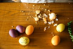 Roztrzaskujący jajko kłaść na stole obok niektóre malujących jajek obraz royalty free