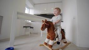 Rozwój dziecka, ślicznej słodkiej chłopiec jeździecki pluszowy koń i ono uśmiecha się w domu w pokoju, zbiory