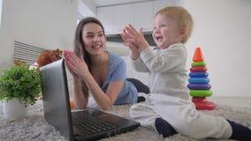 Rozwój dziecka, ciekawa wesoło dziecięca chłopiec z młodymi mamy pchnięcia guzikami laptopy i klaśnięcie ręki kłama na podłodze, zbiory