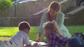 Rozwój dziecka, młoda kobieta czyta ciekawą książkę dla dzieciaków siedzi na zielonym gazonie w naturze w pogodnym świetle zbiory wideo