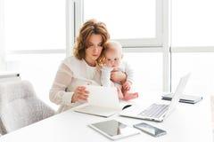 Rozważna biznesowa kobieta trzyma jej ślicznego małego dziecka podczas gdy siedzący przy działaniem i stołem obraz royalty free
