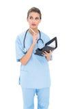 Rozważna brown z włosami pielęgniarka w błękicie szoruje trzymać agendę Obraz Royalty Free