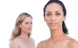 Rozważna brunetka na przedpolu z blondynką na tła spojrzeniu Obrazy Royalty Free