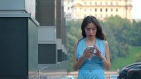 Rozważna brunetki dziewczyna dotyka jej telefon na w błękit sukni ulicznym, super zwolnione tempo strzale, 250 fps zbiory wideo