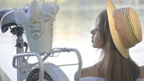 Rozważna brunetki kobieta w słomianym kapeluszu i białej bluzce siedzi blisko jej miasto bicyklu i podziwia rzekę zbiory