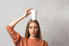 Rozważna dziewczyna z filiżanką kawy na jego głowie Zdjęcie Royalty Free