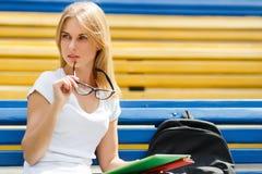 Rozważna dziewczyna z szkłami, siedzi na ławce Fotografia Stock