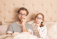 Rozważna lub zanudzający córka w łóżku i ojciec zdjęcia royalty free