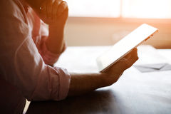 Rozważna męska osoba patrzeje cyfrowy pastylka ekran podczas gdy siedzący w nowożytnym loft wnętrzu przy stołem