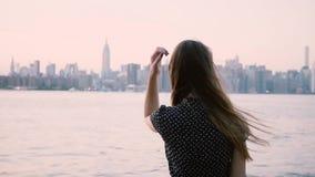 Rozważna młoda Kaukaska dziewczyna z włosianym dmuchaniem w wiatrowym dopatrywanie zmierzchu przy Miasto Nowy Jork brzeg rzecznym zbiory wideo