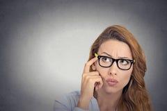 Rozważna młoda kobieta patrzeje wprawiać w zakłopotanie z szkłami Fotografia Royalty Free