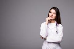 Rozważna, Młoda kobiety lekarka patrzeje daleko od odizolowywający na popielatym tle, Zdjęcia Stock