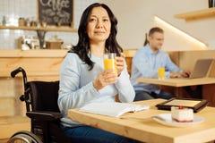 Rozważna niepełnosprawna kobieta pije sok Obraz Royalty Free