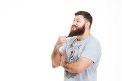 Rozważna przystojna mężczyzna pozycja, macanie i jego broda obraz stock