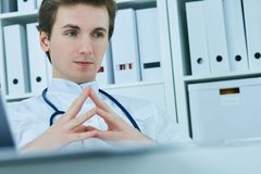 Rozważna samiec lekarka patrzeje oddalony podczas gdy siedzący przy krzesłem w medycznym biurze Fotografia Stock