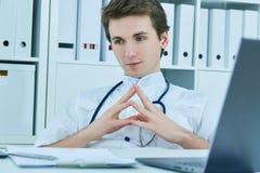 Rozważna samiec lekarka patrzeje oddalony podczas gdy siedzący przy krzesłem w medycznym biurze Obraz Stock