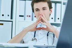 Rozważna samiec lekarka patrzeje oddalony podczas gdy siedzący przy krzesłem w medycznym biurze Zdjęcia Stock