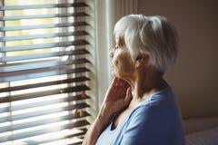 Rozważna starsza kobieta przyglądająca od okno out obrazy royalty free