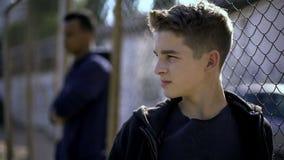 Rozważne nastoletnie chłopiec opiera na metalu ogrodzeniu, spęczenie z przyszłością, sierociniec fotografia royalty free