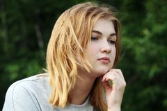 Rozważnej młodej dziewczyny siedzący outside w lecie Obraz Royalty Free