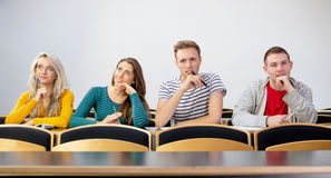 Rozważni uśmiechnięci studenci collegu w sala lekcyjnej Fotografia Stock