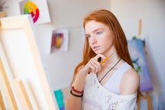 Rozważny ładny młody rudzielec kobiety artysty główkowanie i robić nakreślenia Fotografia Stock