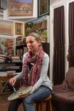 Rozważny żeński malarz patrzeje obrazki w galerii Zdjęcia Stock