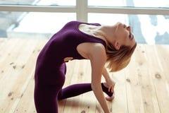 Rozważny atrakcyjnej kobiety obsiadanie na nagiej drewnianej podłodze obrazy stock