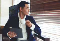 Rozważny azjatykci mężczyzna w eleganckim kostiumu mienia dotyka ochraniaczu podczas gdy relaksujący w nowożytnej kawiarni Zdjęcie Stock