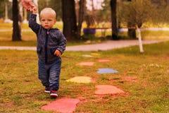 Rozważny berbecia odprowadzenie w jesień parku chwyta ojca ` s ręce i Zdjęcie Royalty Free