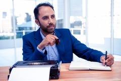 Rozważny biznesmena mienia pióro podczas gdy siedzący przy biurkiem Obrazy Royalty Free