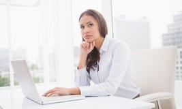 Rozważny bizneswoman używa laptop przy jej biurkiem Zdjęcie Stock