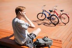 Rozważny chłopiec obsiadanie na ławce i opowiadać na jego telefonie komórkowym z plecakiem beside Młody człowiek z blondynu obsia obraz stock