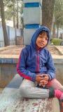 Rozważny chłopiec obsiadanie na ławce w parku fotografia stock