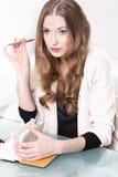 Rozważny dziewczyny obsiadanie przy stołem z notatnikiem i Obraz Royalty Free
