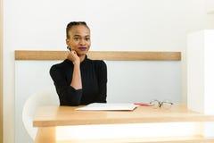 Rozważny elegancki afrykanina lub czerni Amerykański bizneswoman przy biurkiem w biurze Zdjęcia Royalty Free