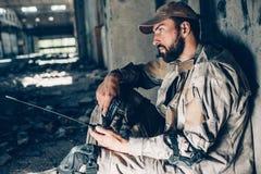 Rozważny facet w mundurze jest siedzący na ziemi i opierać izolować Patrzeje bezpośrednim Wojownik jest zmęczony Obrazy Stock