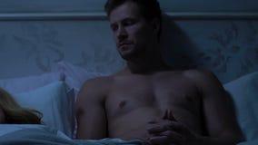 Rozważny męża lying on the beach w łóżku, mężczyzna utrzymuje tajnym od jego żony, żal zbiory
