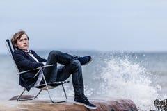 Rozważny mężczyzna obsiadanie na jego krześle przy nadmorski Obrazy Royalty Free
