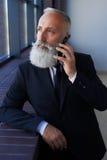 Rozważny mężczyzna opowiada na telefonie z popielatą brodą podczas gdy opierający dalej Obraz Stock