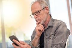 Rozważny mężczyzna patrzeje jego Mobil telefon, lekki skutek Obrazy Stock