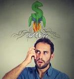 Rozważny mężczyzna przyglądający przy rakietowym dolarowym znakiem nad głowa up obraz stock