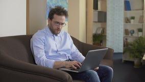 Rozważny męski naukowiec pisać na maszynie nowego artykuł na laptopie, freelance praca zbiory