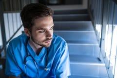 Rozważny męski pielęgniarki obsiadanie na schody Obrazy Royalty Free