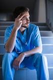 Rozważny męski pielęgniarki obsiadanie na schody Zdjęcie Stock