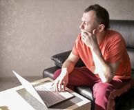 Rozważny młodego człowieka obsiadanie blisko laptopu w jej żywym pokoju, Copyspace obrazy royalty free