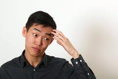 Rozważny młody Azjatycki mężczyzna dotyka jego czoło zdjęcia stock