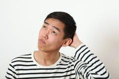 Rozważny młody Azjatycki mężczyzna patrzeje oddolny zdjęcie stock